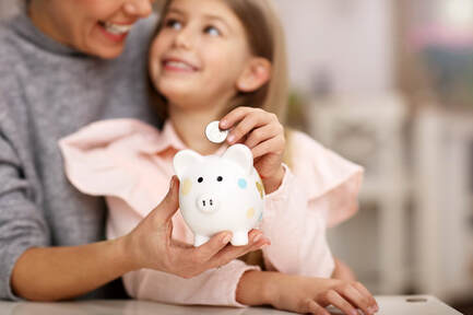 Picture of a mother holding her daughter while the child places a coin inside her piggy bank