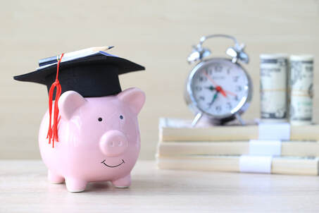 Picture if a piggy bank wearing a graduation cap sitting in front of a stack of money