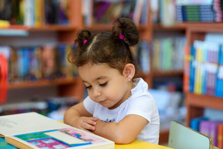 Picture of a female child reading a book in a library