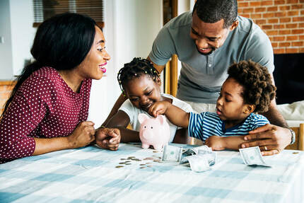 Picture of a mom and dad at a table with their two children while the children count money and place it into their piggy bank