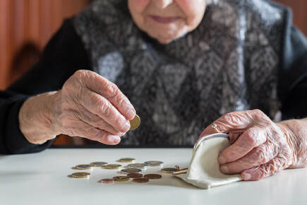 Picture of elderly woman sitting at a table placing coins into her white change purse